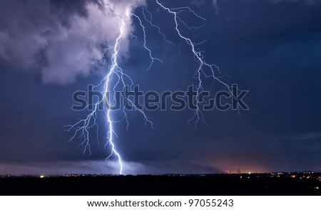 Big lightning in the stormy sky over a city - stock photo