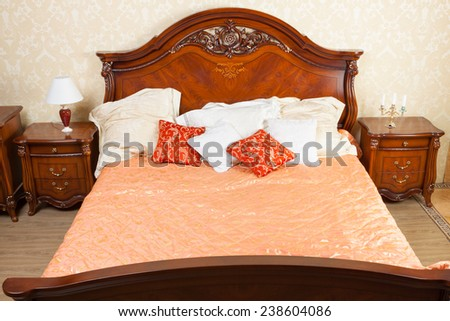 big luxurious double bed in the interior - stock photo