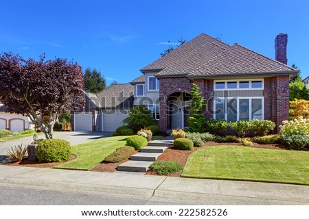 Big luxury house with tile roof and brick wall trim. Walkway decorated with flower pots - stock photo