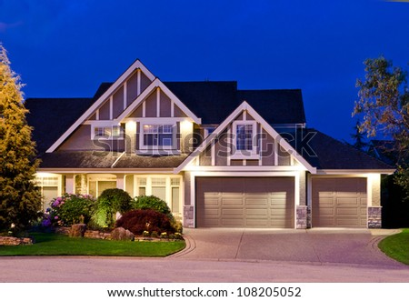 Big luxury house with triple garage doors at dusk, night in suburbs of Vancouver, Canada - stock photo