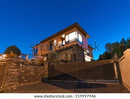 Big luxury modern house behind the gates at dusk, night time in suburbs of Vancouver, Canada. - stock photo