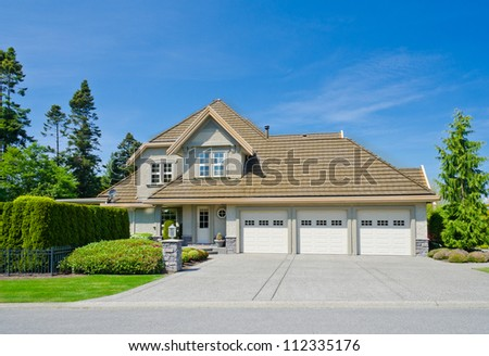 Big luxury triple garage doors house in a residential neighborhood. Vancouver Canada.