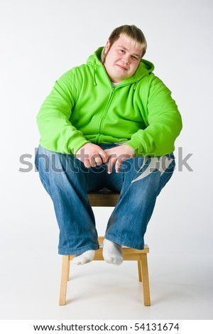 Big man in a green jacket sitting on a chiar