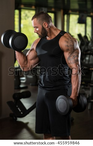 Big Man Standing Strong In The Gym And Wxercising Biceps With Dumbbells - Muscular Athletic Bodybuilder Fitness Model Exercise Bicep - stock photo