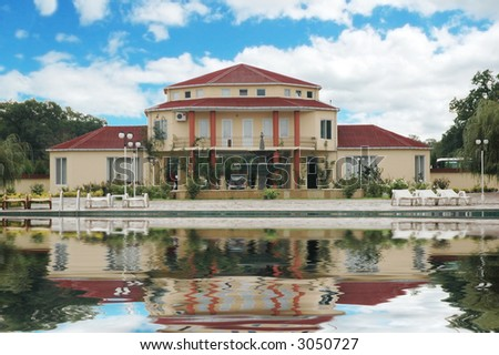 Big mansion and swimming pool  in the summer - stock photo