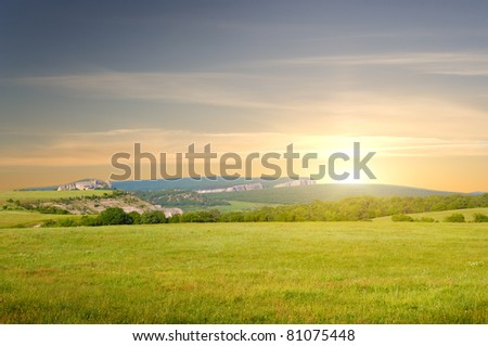 Big meadow on sunrise on mountain background. Composition of nature.