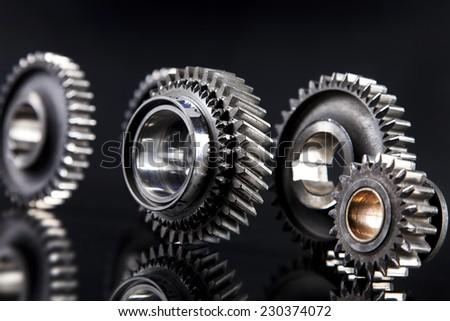 Big metal gears on glossy black background - stock photo