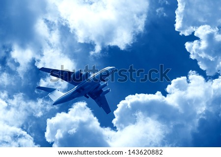 Big modern jet plane flying in storm sky with clouds - stock photo