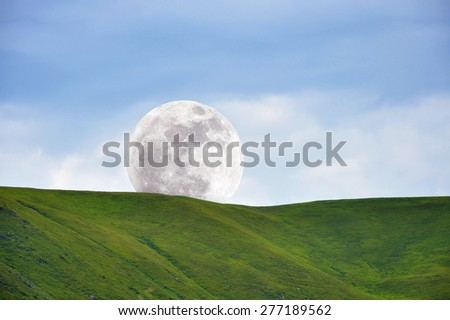 Big Moon in the day sky behind green slope - stock photo