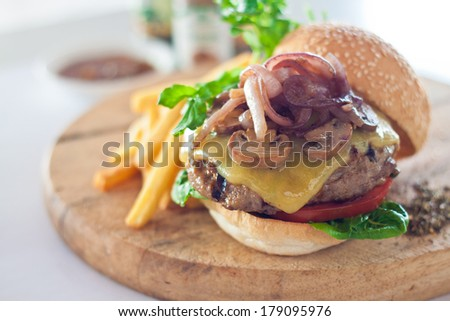 Big mouth cheese burger served with french fries on wooden cutting board. - stock photo