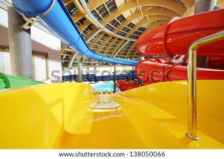 Big multi-colored indoor water slides in aquapark. Descent yellow slide. - stock photo