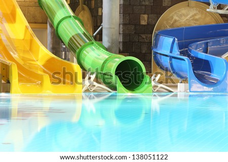 Big multi-colored water slides and pool in indoor aquapark. Yellow, green and blue slides. - stock photo