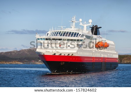 Big Norwegian passenger cruise ship sails in fjord - stock photo