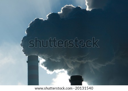 Big nuclear plant smokestack whit sun on the background