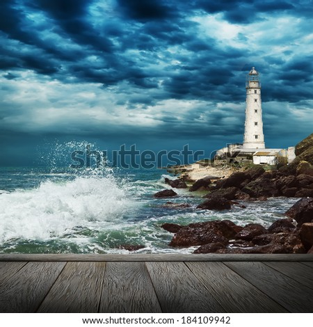 Big ocean wave breaking the shore near lighthouse and wood pier - stock photo