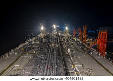 Big oil tanker moored to berth at night and ready to transfer the cargo to the terminal. - stock photo