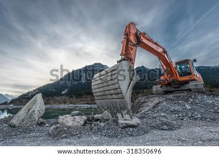 big orange digger on gravel heap with big shovel - stock photo