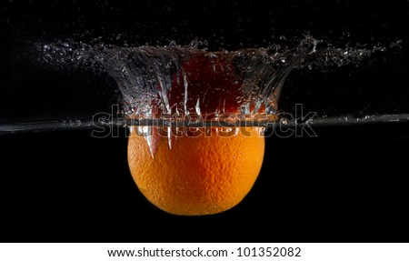 big orange dropped in fish tank filled with water - stock photo