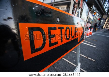 Big orange sign Detour in the middle of the street - stock photo