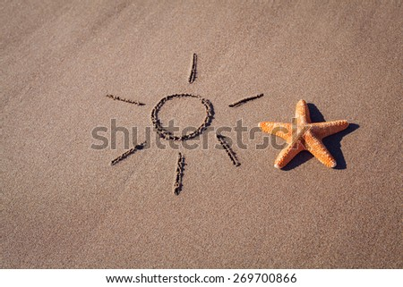 big orange starfish and sun drawing on the seashore - stock photo