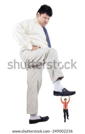 Big overweight businessman put his foot over his rival, symbolizing business competition - stock photo