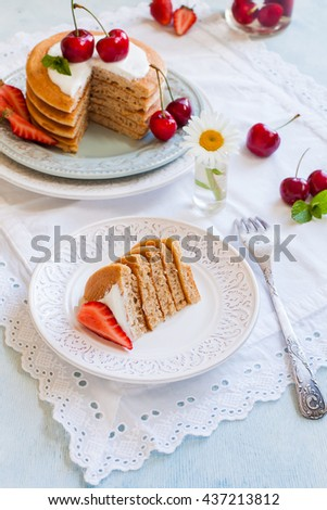 Big pancakes with yogurt and berries, cut pieces on the separate plate