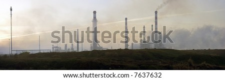 Big panorama of a refinery at dawn (first rays of the morning sun) - stock photo
