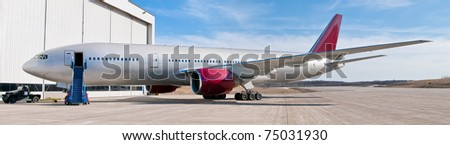 Big passenger  airplane red and white parked near hangar - stock photo