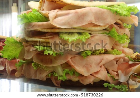 big piadina tortillas of bread  with ham and salad  for sale in the cafeteria
