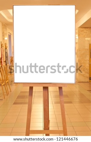 big picture frame with white cut out canvas on easel with yellow light gallery background - stock photo