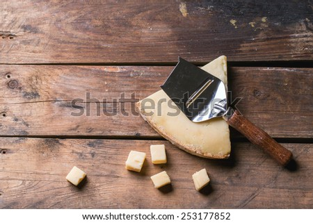 Big piece and little cubes of Belgian cheese with cheese knife over wooden background. Top view. - stock photo
