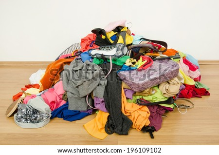 Big pile of clothes and accessories thrown on the ground. Untidy cluttered woman wardrobe all on the floor. - stock photo
