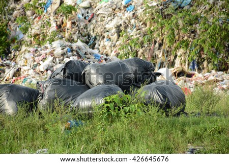 Big pile of garbage and waiste in black bags - stock photo