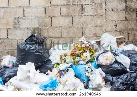 Big pile of garbage and waiste in black bags, copyspace on the wall as background - stock photo