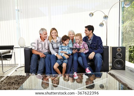 Big playing family with tablet PC in a living room - stock photo