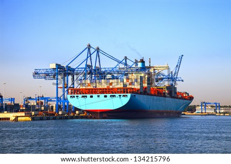 Big port cranes and a Container Ship. - stock photo
