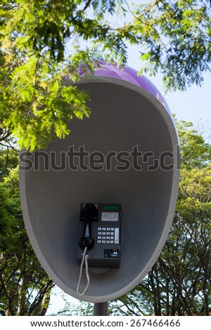 Big public purple street pay phone with trees - stock photo