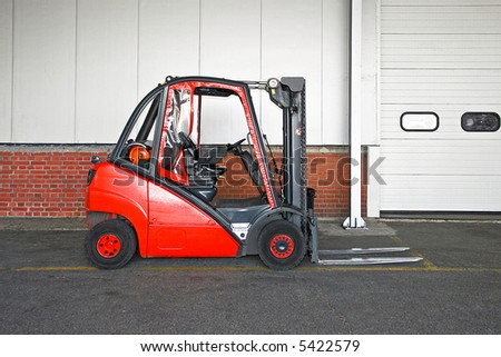 Big red fork lifter truck in storehouse - stock photo