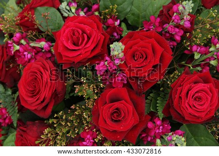 Big red roses and pink decoration in a wedding flower arrangement