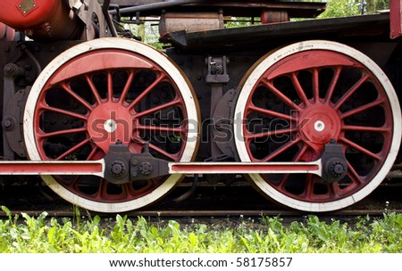 big red rusty wheels of old steam engine - stock photo