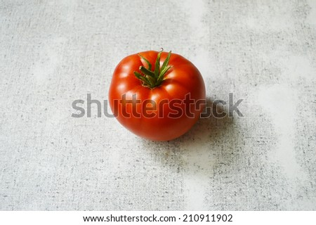 big red tomato on a white table close up - stock photo