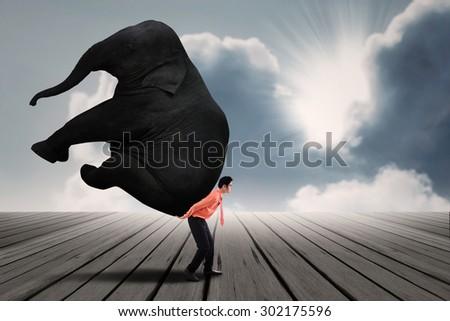 Big responsibility: Portrait of businessman carrying heavy elephant under blue sky - stock photo