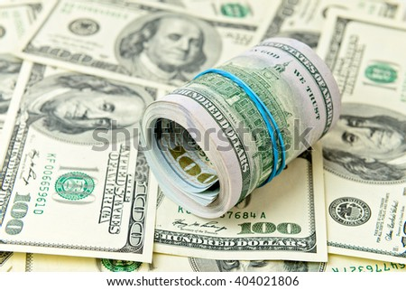 Big roll of dollars bills over banknotes - stock photo
