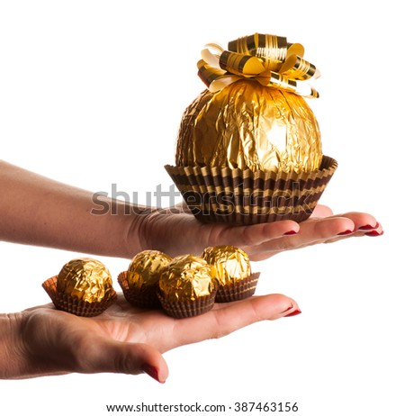 Big round chocolate candy wrapped in golden foil with big bow on top lying in one palm in the other are small candy looking like babies isolated over white. - stock photo