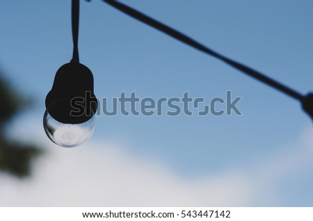 Big round Lightbulbs on wire hanging in the air with blurred blue cloudy sky background