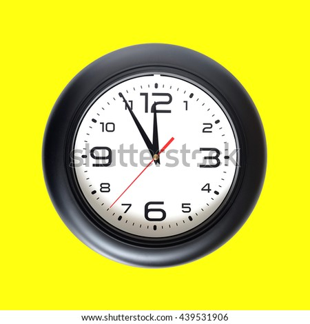 Big round wall clock, with a black rim isolated on yellow background close-up and arrows showing almost twelve o'clock - stock photo