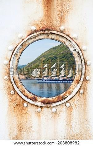 Big sailing ship behind round rusted porthole on white wall  - stock photo