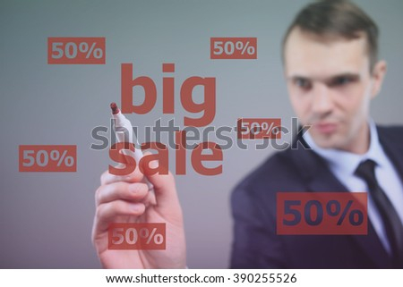 BIG SALE - Businessman writing text on a transparent board
