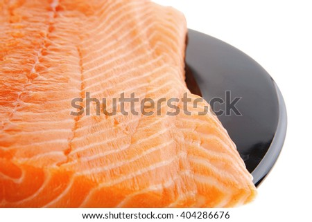 big salmon chunk on black plate over white - stock photo
