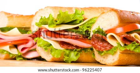 big sandwich with fresh vegetables on wooden board